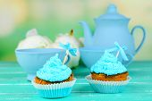 Tasty cup cakes with cream on blue wooden table