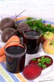 Glasses of fresh beet juice and vegetables on napkin on wooden background