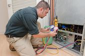 image of hvac  - HVAC technician charging a heat pump with refrigerant - JPG