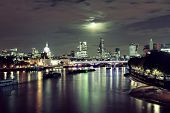 London cityscape with urban buildings and moon over Thames River at night