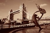 Tower Bridge and girl, dolphin statue over Thames River in London.