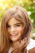 Closeup portrait of smiling cute little girl having fun outdoors, playing in summer park, enjoying s