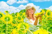 Portrait of cute girl in sunflowers field, holding in hands one big yellow flower, bright sunny day,