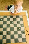 picture of draught-board  - Draughts board game. Little boy clever child kid playing checkers thinking outdoor in the park. Childhood and development