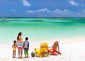 Family of mother and kids enjoying vacation at tropical beach with two colorful wooden chairs on whi