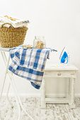 stock photo of peg  - Jar of clothes pegs and basket of fresh laundry with iron in the background - JPG