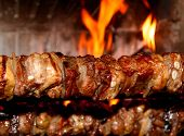 picture of spit-roast  - spit roast with of tasty meat cooked on a spit in the fireplace 1