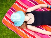 Teenage Girl With A Hat Covering Her Face Lying On Her Back On A Colorful Rug In The Grass