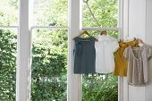 Blouses and skirt on hangers at domestic window