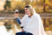 happy couple sitting together by the autumn lake with blanket