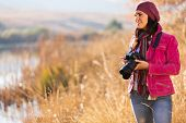 young female photographer holding a camera outdoors in autumn