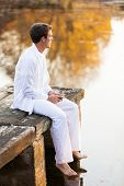 thoughtful young man sitting on wooden pier and drinking wine by the lake