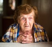 Close-up emotional old woman sitting at table in his house.