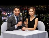 restaurant, couple and holiday concept - smiling young couple with glasses of red wine looking at ea