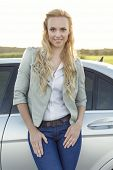 Portrait of attractive young woman standing by car at countryside