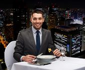 restaurant, people, technology and holiday concept - smiling man with tablet pc eating main course at restaurant