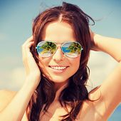 holidays, travel, vacation and happiness concept - beautiful woman in sunglasses with beach reflecti