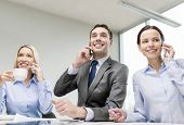 business, technology and office concept - smiling business team with smartphones making calls in off