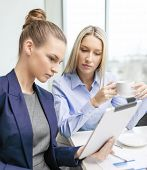 business, technology and office concept - serious businesswomen with tablet pc computers having disc