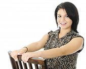 A beautiful teen girl happily holding on as she sits and leans backwards on a wooden chair.  On a wh