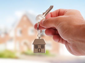 stock photo of in front  - Holding house keys on house shaped keychain in front of a new home - JPG