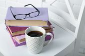 Pile of books with cup and glasses on the chair on brick wall background