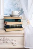 Composition of books and cup on the windowsill on light background