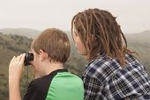 two youth looking for wildlife at a lookout point in the mountains.