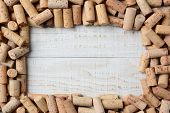 Overhead shot of a group of wine corks forming a frame on a rustic whitewashed wood table. Horizontal format.