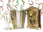 New Year champagne bottle in cooler, two champagne glasses and table clock showing midnight shot on white