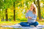 Happy Young Pregnant Girl With A Notebook In A Park