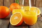 Glass of orange juice with slices on rustic wooden table background