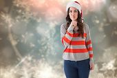 Festive brunette in santa hat keeping a secret against blurred christmas background