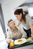 Homecarer preparing lunch for elderly woman