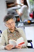 Elderly woman reading book, home helper in background