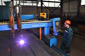 Metalwork Plant, Worker Controls System Thermal Cutting Of Metal Sheets.