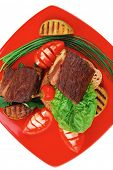 barbecued meat : beef ( lamb ) garnished with baked apples , fresh raw tomatoes, hot pepper, on bread, over red plate isolated on white background
