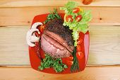 hot beef on red plate over wood table
