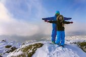 Cheerful couple snowboarders standing on the mountain
