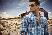 picture of check  - Handsome fashionable man in sunglasses and a blue checked shirt posing outdoors with a wooden cabin behind and copyspace looking into the centre of the frame - JPG