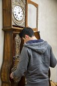 picture of pendulum clock  - Young man checking the pendulum and winding the mechanism on a vintage long case clock standing with his back to the camera as he works - JPG