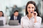 stock photo of telemarketing  - Portrait of happy smiling female customer support phone operator at workplace - JPG
