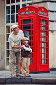 foto of phone-booth  - Happy father and son outdoors in city by red phone booth - JPG