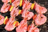 foto of bbq party  - Skewered Big Shrimps On The Hot BBQ Grill In The Background - JPG