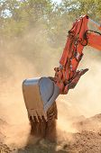 foto of track-hoe  - Large track hoe excavator moving rock and soil for fill for a new commercial development road construction project - JPG