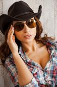 foto of cowgirls  - Beautiful young cowgirl adjusting her eyewear and looking at camera while standing against the wooden background - JPG