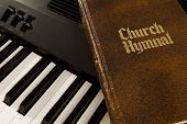 stock photo of minstrel  - a church hymnal sitting on top of a keyboard - JPG