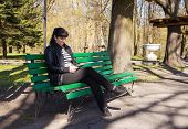 image of black pants  - young beautiful woman in a black leather jacket and black pants sitting on a park bench holding a tablet - JPG