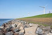 Endless Dike With Windmills With Lonely Bicycle