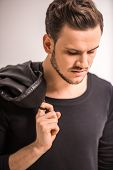 stock photo of down jacket  - Portrait of handsome man is holding leather jacket and looking down - JPG